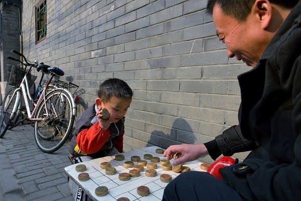 Father and son playing Chinese chess in the hutongs