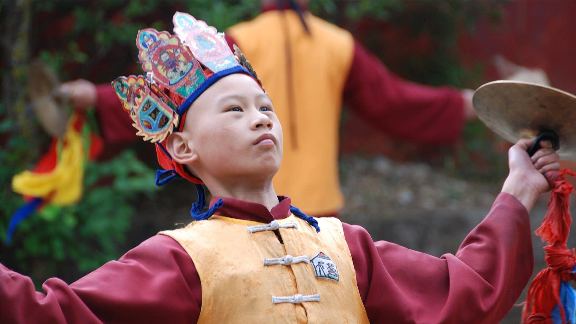 Dongba (Shaman)~Dongba, translated into English as shaman, come in many forms. Though some claim to access the spirit world, this young boy is at a seminary studying how to perform the official functions (e.g. births, deaths & marriages) of a religious functionary.
