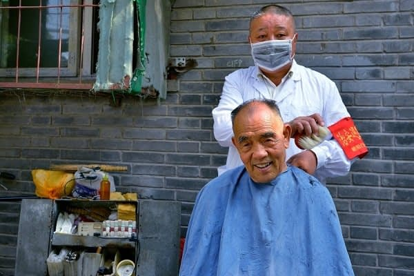 Local street barber at work in the hutongs