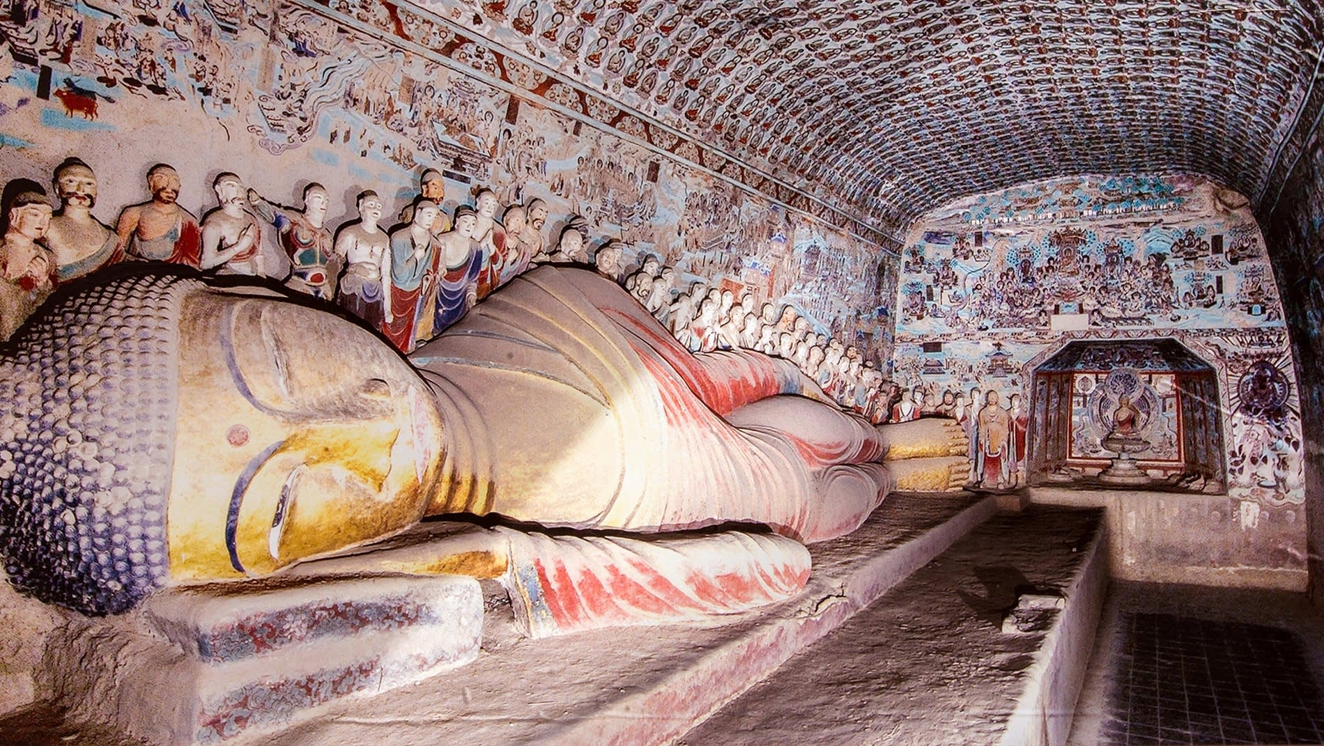 Mogao Caves~The caves span a millennium of history during which time architecture, styles, subjects and painting techniques all evolved. This cave dates from thehigh Tang period (705 - 781), and features a reclining Buddha.