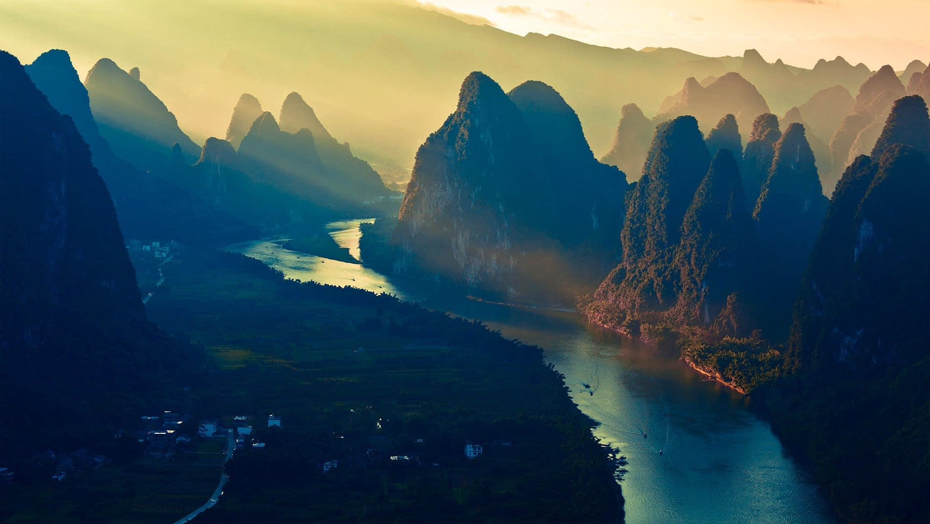 Karst Mountains~The erosion of a massive limestone block over tens of millions of years has left a phantasmagorical landscape of vegetation-encrusted towers and cones sowed together by a meandering river irrigating bountiful fields of fruit, rice and vegetables.